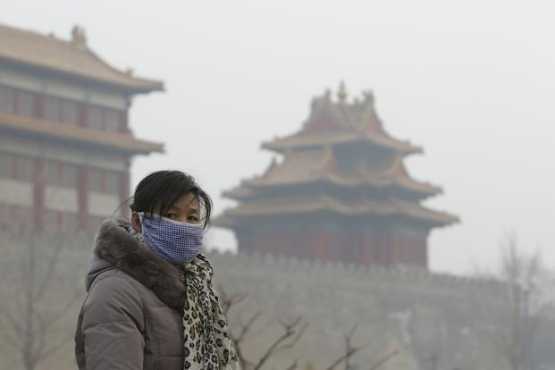 A visitor wearing a mask walks outside the Forbidden City in Beijing. In 2012, air pollution killed some 8,600 people prematurely and cost $1 billion in economic losses, according to a study by Beijing University and Greenpeace. Reuters