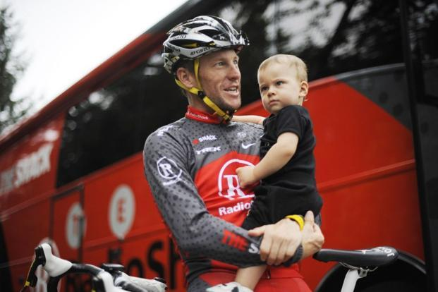 20 July 2010: Armstrong carries his one year-old son, Max, before participating in a training session during a rest day of the 2010 Tour de France cycling race at the hotel hosting the US cycling team in Southwestern France. AFP