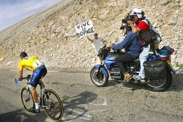 21 July 2002:  Armstrong next to a banner against doping during the 89th Tour de France. Armstrong, 41, now plans to testify against officials from the International Cycling Union about their involvement with doping in cycling. AFP
