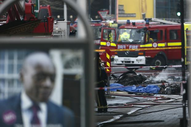 Smoke rises from debris as police and emergency services attend the scene of a helicopter crash in London. Photo: Reuters