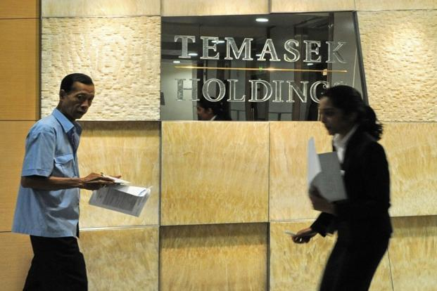 Office workers walk past a Temasek Holdings sign in Singapore. Photo: Roslan Rahman/AFP