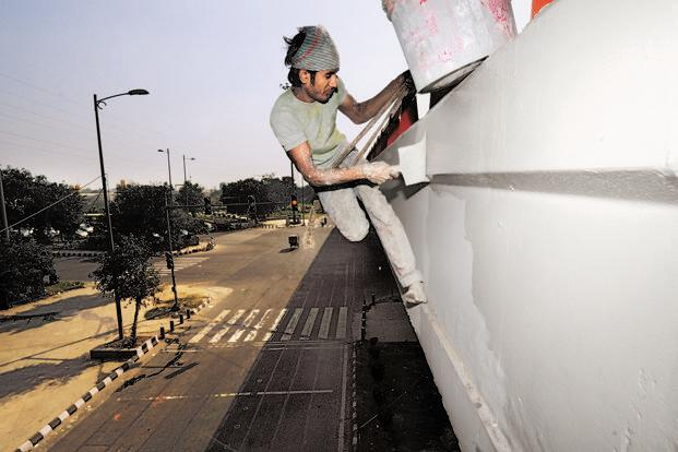 With seven years' experience, painter Faishal glides across the side of the Nizamuddin flyover, Delhi, with a brush in hand