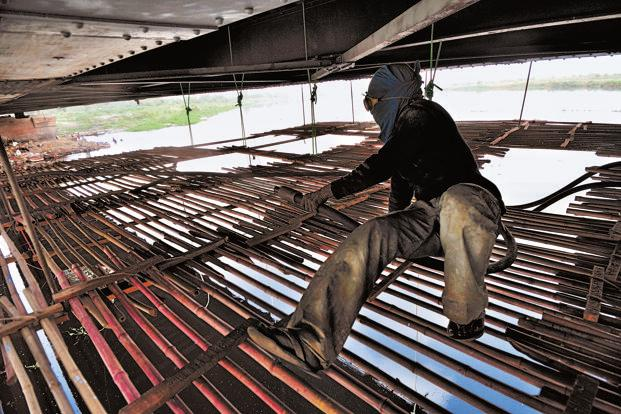 Sandblasting is used to clean the metal surfaces and prevent rust formation. Gulab Kumar is squatting on a handmade bamboo platform, suspended under the iron bridge over the Yamuna, Delhi, as he works