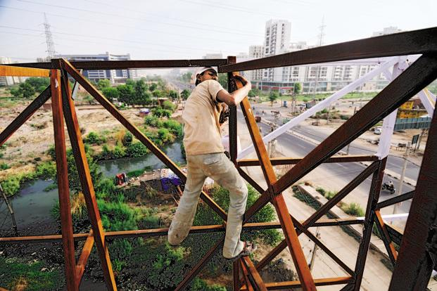 Sanjay paints a hoarding frame on Sohna Road, Gurgaon, without any harness to keep him from falling, for a mere Rs 300 a day