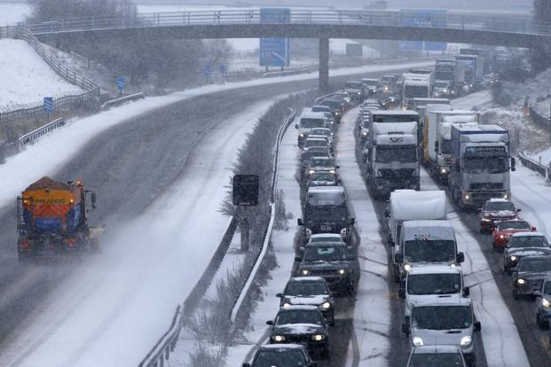 A snow plough is driven past standing traffic on the M40 near Warwick, central England on Friday. Photo: Reuters