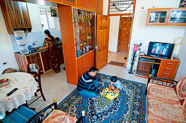 Shambhu ST with his family at his VBHC flat. The 35-year-old's compact, two-bedroom apartment on the outskirts of Bangalore is newly constructed, well-lit, ventilated and secure. He bought the flat for `11 lakh. Photo: Aniruddha Chowdhury/Mint (Aniruddha Chowdhury/Mint)