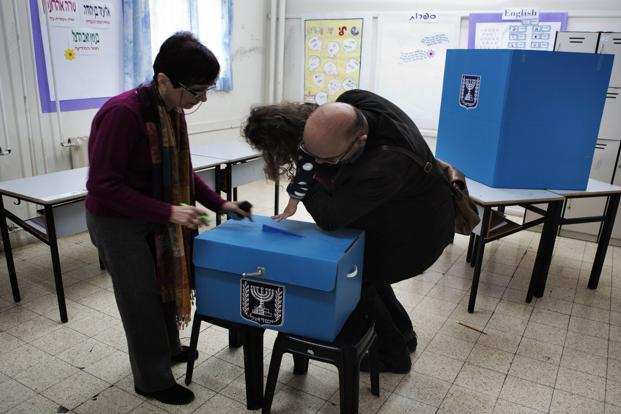 A girl casts her father's vote in Jerusalem on Tuesday as Israel residents started to vote for the 19th Israeli general election. Photo: AFP
