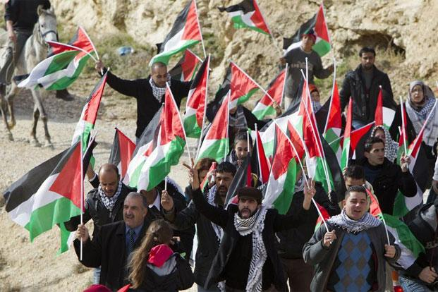 Palestinians along with Israeli and foreign activists wave Palestinian flags shouting slogans during a gathering at Bab al-Shams between Jerusalem and the Jewish settlement of Maale Adumim in the Israeli-occupied West Bank, in January. Photo: AFP