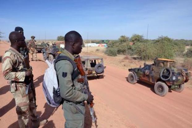 Malian soldiers watch a French military unit near Diabaly (400km north of Bamako) on Wednesday. Photo: Eric Feferberg/AFP