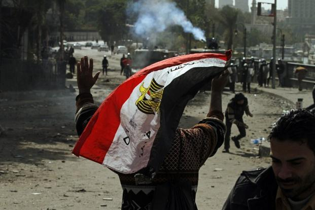An Egyptian protester waves the national flag as he gestures towards riot police during clashes near Cairo's Tahrir Square on Monday. Photo: AFP