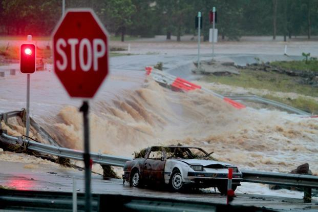 Floodwaters race across the Oxenford-Tamborine road on Australia's Gold Coast on Monday as severe floods swept through two states. Photo: AFP