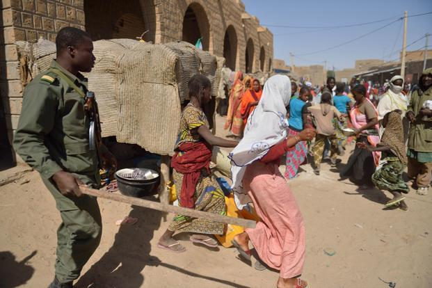 A Malian soldiers tries to disperse the crowd on Tuesday in Timbuktu as residents plunder stores they say belong to Arabs, Mauritanians and Algerians who they accuse of supporting the al Qaeda-linked Islamists. Photo: AFP