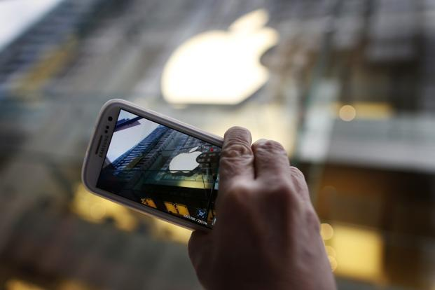 A passerby photographs an Apple store logo with his Samsung Galaxy phone. Photo: Reuters
