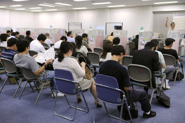 Unemployed Japanese people search through job vacancies at an employment bureau in Tokyo. Photo: AFP