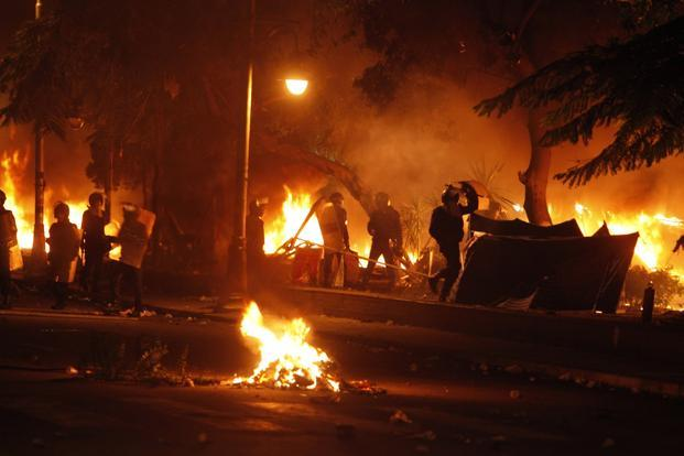 Police burn tents of protesters who staged a sit-in for weeks in front of the presidential palace, during clashes between protesters and police, in Cairo on Friday. Photo: Reuters