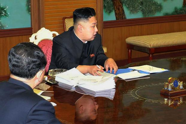 The photo released by the North's state media showed Kim with a black smartphone on the table next to his arm—as well as a lit cigarette. Photo: AFP.