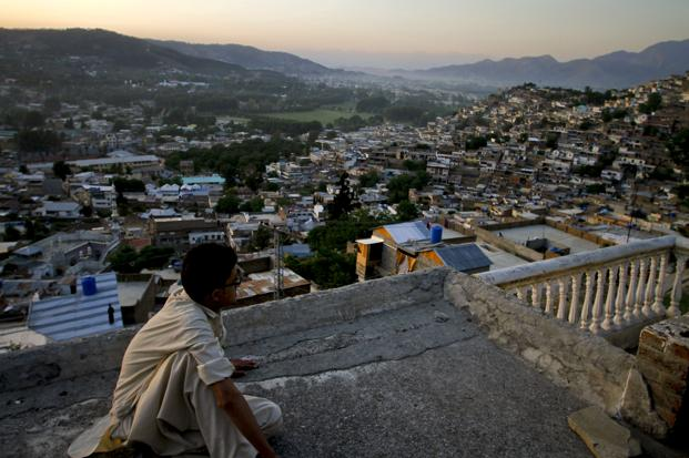 A boys sits on the rooftop of his house as he views the city of Abbottabad. Photo: AP