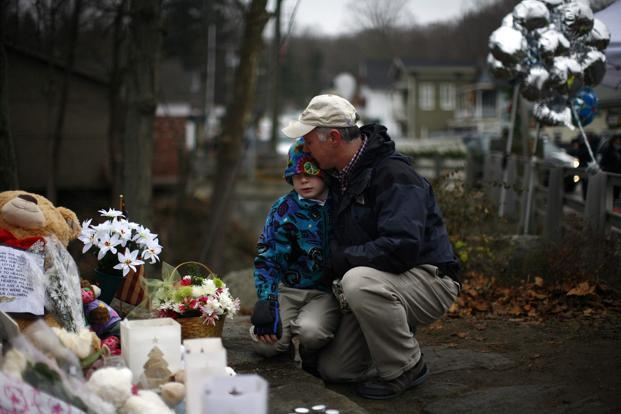 A file photo of a man hugging a boy at a memorial near Sandy Hook Elementary School in Newtown. Photo: Reuters