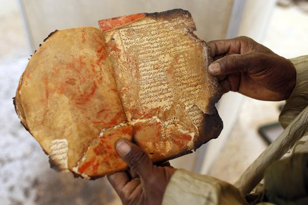 A museum guard displays a burnt ancient manuscript at the Ahmed Baba Institute in Timbuktu. UNESCO believes most of some 300,000 centuries-old texts, ranging from scholarly treatises to old commercial invoices, are safe. Photo: Reuters