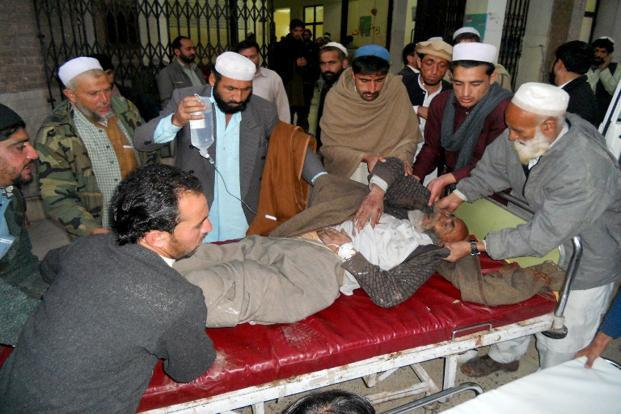 Pakistani men move an injured bomb blast victim at a hospital in Kohat on Friday after a bomb explosion in Orakzai district.Photo: AFP