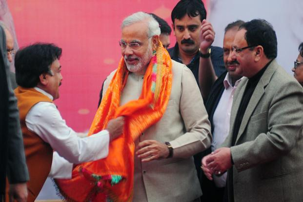 Narendra Modi is greeted by party workers at BJP headquarters after he was re-elected as the chief minister of Gujarat. Photo: Ramesh Pathania/Mint