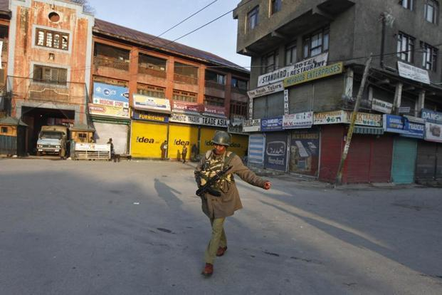 A policeman patrols a deserted road in Srinagar on Friday. Photo: Reuters