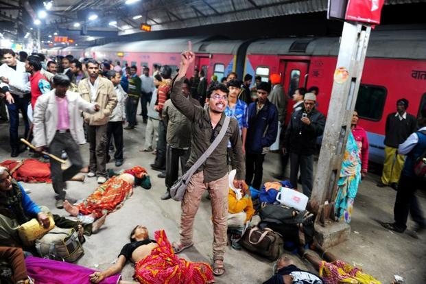 A man denounces the police for the stampede that killed one of his relative at the main railway station in Allahabad, even as bodies of other victims lie around. AFP