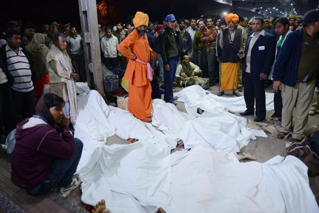 Authorities stand among the bodies of the pilgrims that were killed during a rush-hour stampede at the railway station in Allahabad on the evening of 10 February 2013. AFP