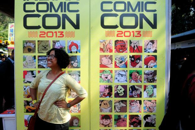 A visitor poses in front of one of the Comic Con posters