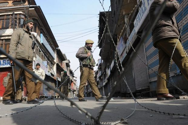 Police patrol a deserted street during a curfew in Srinagar. Photo: AFP