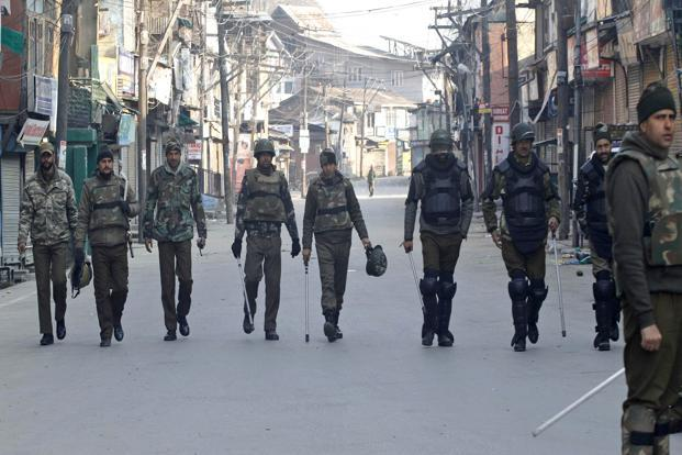 Police patrol a street on the second consecutive day of curfew in Srinagar on 10 February. Mobile Internet services remained down for the third day as a precautionary measure and newspapers also failed to hit stands on Monday due to the curfew. Photo: AP