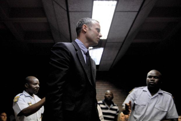Oscar Pistorius leaves the court room after his hearing on Friday. South African prosecutors will argue that Pistorius is guilty of premeditated murder in his girlfriend's death. Photo: Stephane de Sakutin/ AFP
