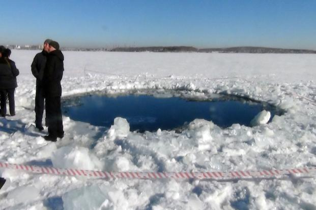 People standing near a six-metre (20-feet) hole in the ice of a frozen lake, reportedly the site of a meteor fall, outside the town of Chebakul in the Chelyabinsk region. Photo: AFP