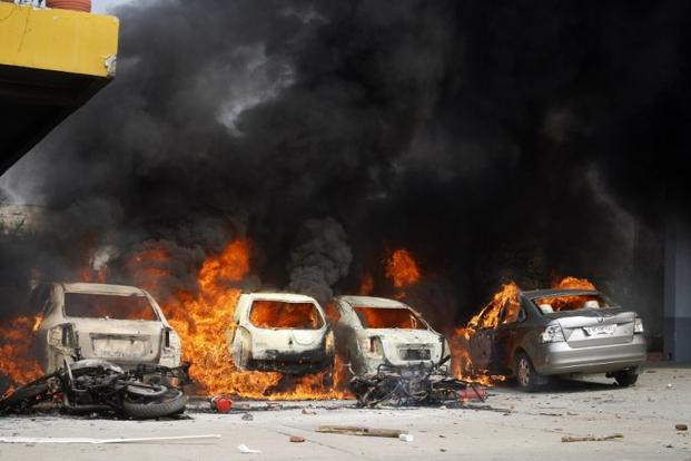 Cars burn in the parking lot of an Indian factory on the first day of the 2-day trade union strike in Noida. In addition, factories were stoned when violence broke out in the suburbs of the capital. AFP