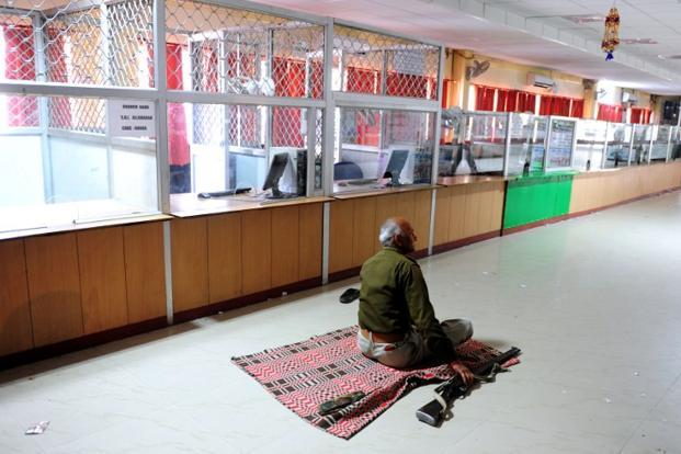 A security guard sits on a mat in a deserted SBI Bank branch in Allahabad The bandh was called by various trade unions to protest against what they called the anti-labour policies of the government. AFP