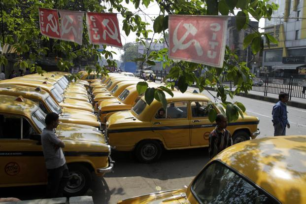 Commuters in Kolkata wait for transport beside parked taxis during the first day of a two-day nationwide strike called by trade unions. AP