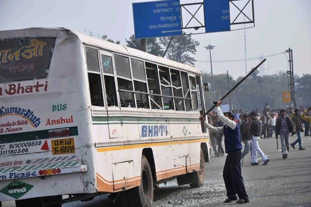 Protesters damaging a bus during a nation-wide strike called by traders union at an industrial area in Noida phase-II on Wednesday. Photo: PTI