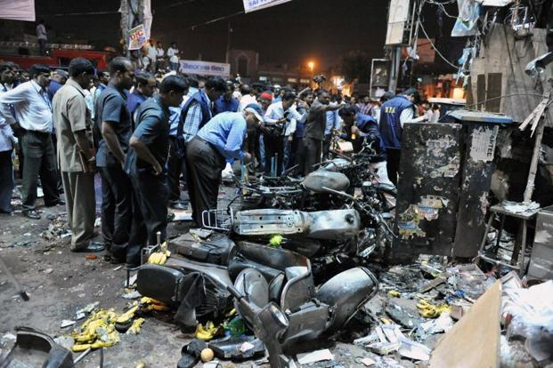 Police and locals investigate the site of the twin bomb blasts at Dilshuk Nagar in Hyderabad on Thursday. The mangled vehicles point to the intensity of the blasts that took place within minutes of each other. AFP