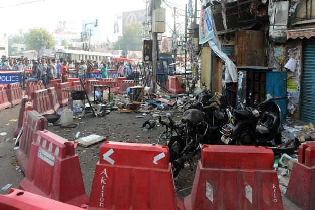Police and pedestrians look on at the site of the bomb blast at Dilsukh Nagar in Hyderabad on Saturday. Photo: AFP