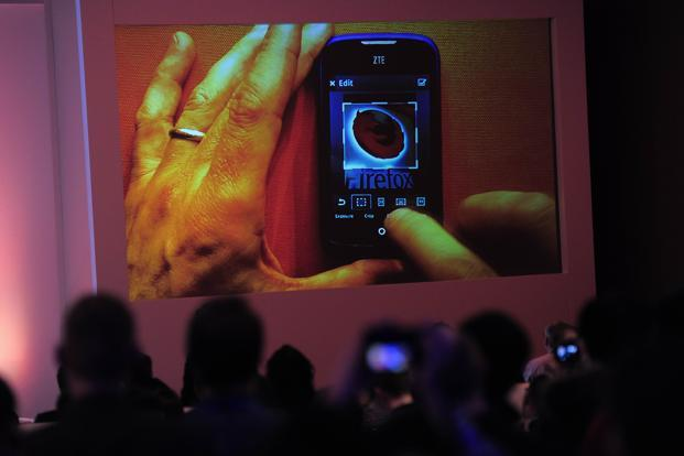 People look at a screen displaying a ZTE mobile phone with a Firefox logo on its screen during a press conference to present the new Firefox OS mobile operating system in Barcelona. Photo: AFP