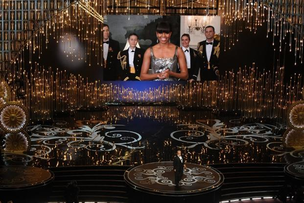 US First Lady Michelle Obama, on a video screen, announces the Oscar for Best Movie along with actor Jack Nicholson onstage at the Oscars. AFP PHOTO/Robyn BECK