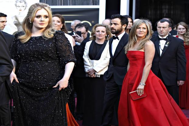 Singer Adele (Left) and actress Jennifer Aniston arrive on the red carpet. Aniston sports a red Valentino gown, while Adele wears a Jenny Packham dress. Reuters
