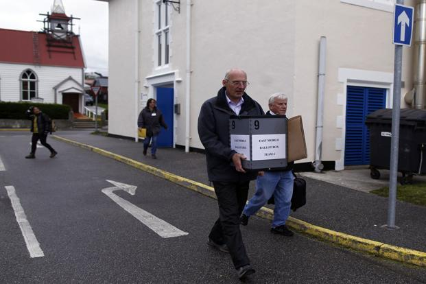 Referendum volunteer Jack Harris leaves the Town Hall with a mobile ballot box to take it to remote polling stations in Stanley. Photo: Reuters