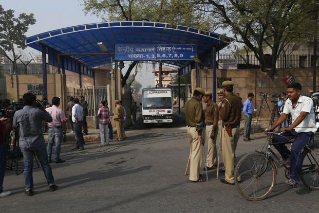 Indian police men and media persons stand outside the Tihar Jail in New Delhi on Monday. Photo: AP
