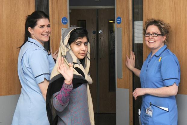 Malala waves as she is discharged from the Queen Elizabeth Hospital in Birmingham in central England on 3 January 2013 where she was admitted for her treatment following the attack on her by the Taliban. AFP