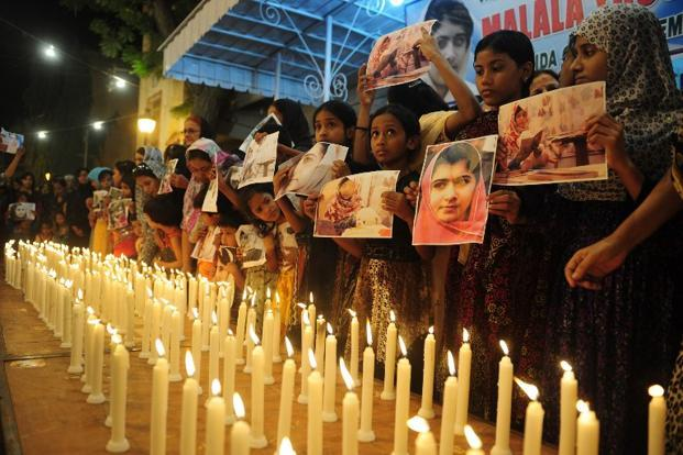 "Supporters of Malala burn candles during a ceremony to mark ""Malala Day"" in Karachi on 10 November 2012. On the day a special UN petition was launched using the slogan ""I am Malala"" to promote education worldwide. AFP"
