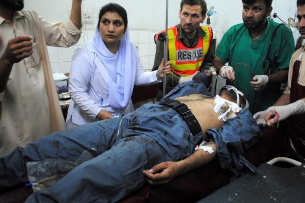 Pakistani paramedics give treatment to an injured blast victim at a hospital following a suicide attack in Peshawar on Friday. Photo: AFP