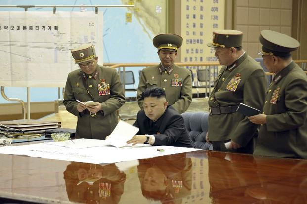 North Korean leader Kim Jong-Un discusses the strike plan with North Korean officers on 29 March. North Korea on 5 April said that it cannot guarantee safety of foreign embassies. AFP/KCNA.