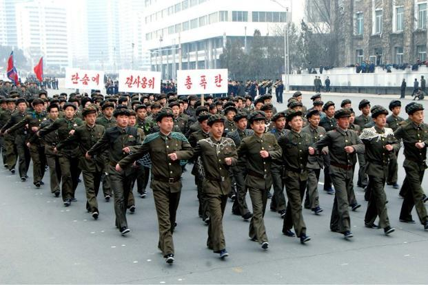 North Korean students march at the Kim Il-Sung Square in Pyongyang while singing wartime songs in chorus on 17 March. Despite Pyongyang's sabre rattling, the armistice between the two continues to hold,  AFP/KCNA