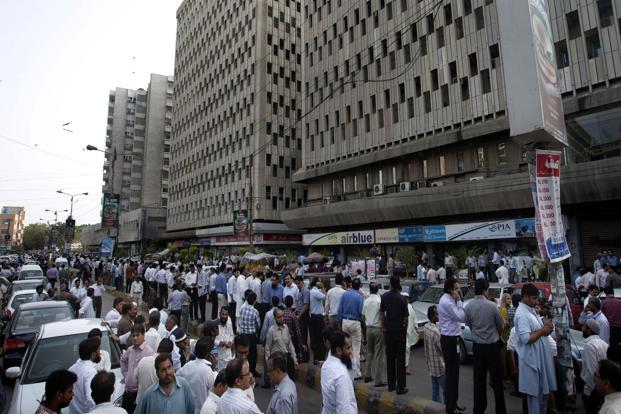 People evacuate buildings and gather on road after a tremor of an earthquake was felt in Karachi, Pakistan on Tuesday. Photo: AP